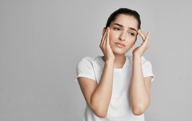 Donna in maglietta bianca vista ritagliata mal di testa problema di salute. foto di alta qualità