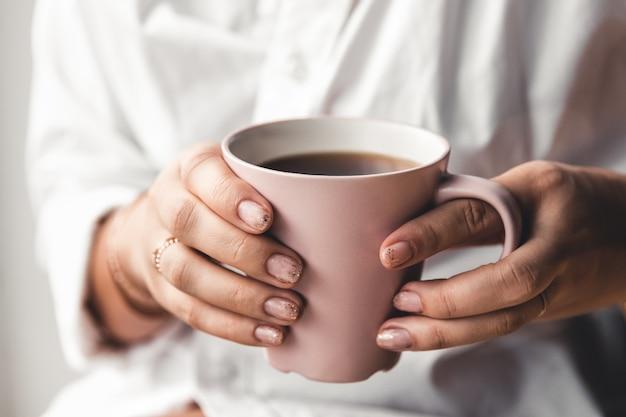 La donna in una maglietta bianca tiene il caffè del mattino in una tazza di ceramica rosa. manicure. vista frontale