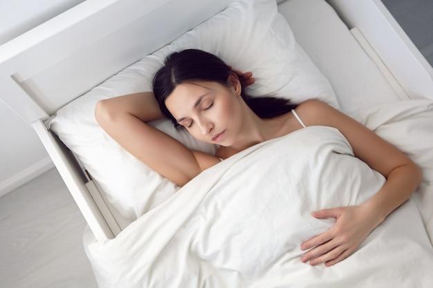 La donna in una maglietta bianca è sdraiata sul letto e un cuscino è sotto la coperta nella stanza