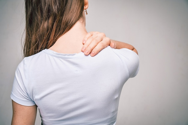 Donna in maglietta bianca si massaggia il collo per la fatica.