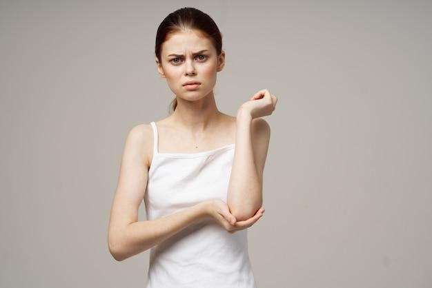 Donna in t-shirt bianca problemi con l'osteoporosi del dolore dei tronchi