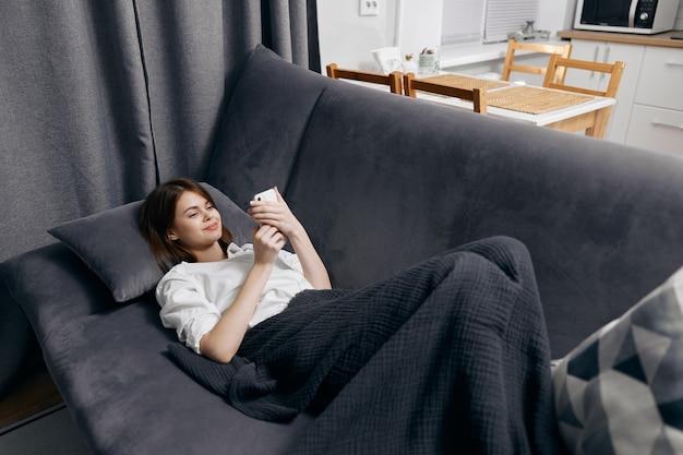 La maglietta bianca della donna con un telefono in sua mano si trova sul divano