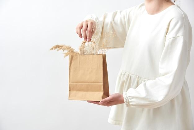 Una donna con un vestito di tessuto bianco tiene tra le mani una borsa ecologica di carta con un ramoscello secco di pianta naturale, copia spazio. concetto di eco naturale.