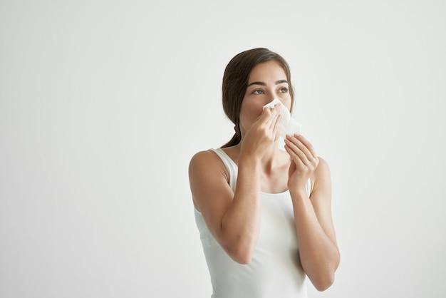 La donna in una maglietta bianca si soffia il naso in un'infezione da medicina per il raffreddore del velo
