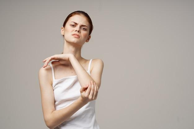 Donna in maglietta bianca dolore al gomito artrite malattia cronica sfondo chiaro
