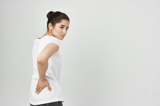 Donna in maglietta bianca problemi di salute mal di schiena
