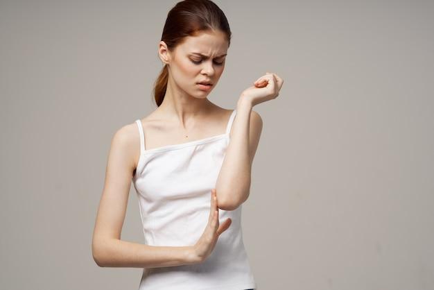 Donna in maglietta bianca che si aggrappa al gomito problemi di salute trattamento congiunto studio trattamento