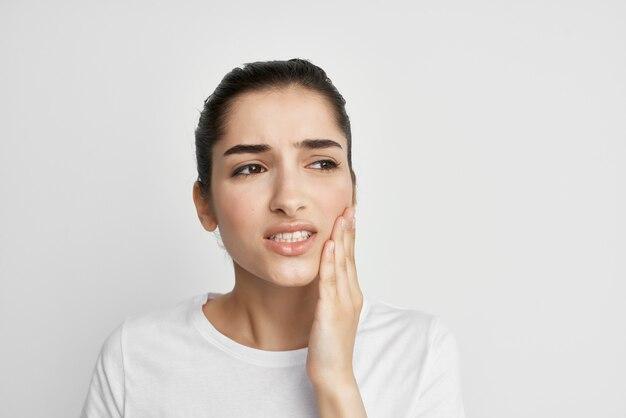 Donna in maglietta bianca che tiene il trattamento di odontoiatria mal di denti del viso