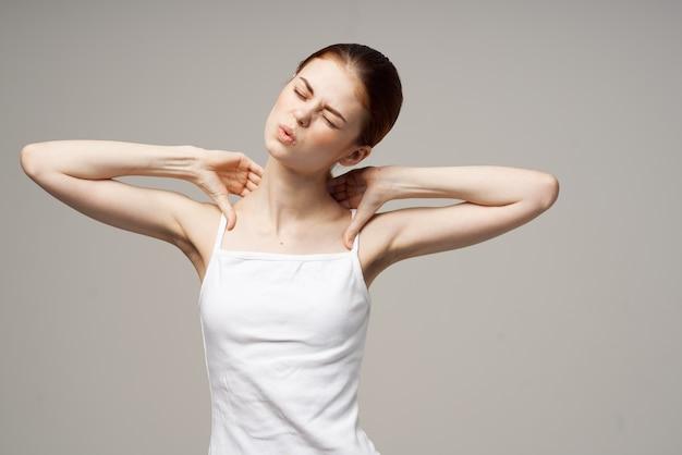 Donna in maglietta bianca che si aggrappa al collo problemi di salute trattamento congiunto in studio