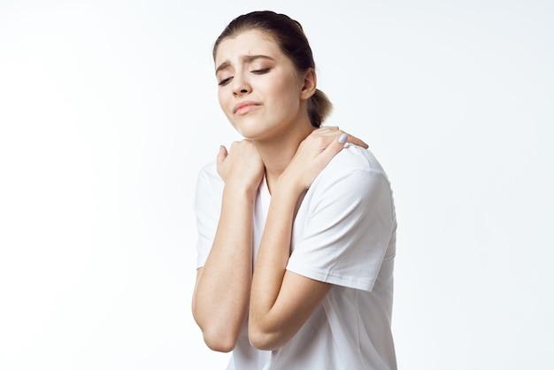 Donna in maglietta bianca che tiene le spalle dolore al collo problemi di salute disagio