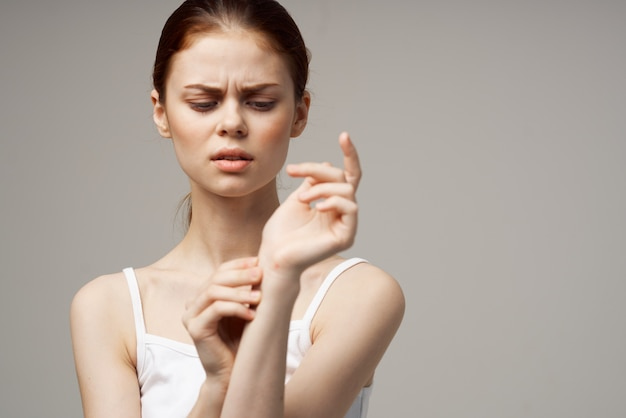 Donna in maglietta bianca reumatismi dolore al braccio problemi di salute isolato sfondo