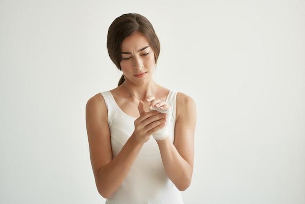 Donna in maglietta bianca trattamento farmaco problemi di salute sfondo chiaro