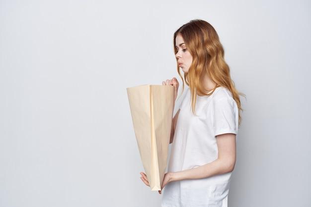 Donna in maglietta bianca con un pacchetto di spesa per l'imballaggio della spesa