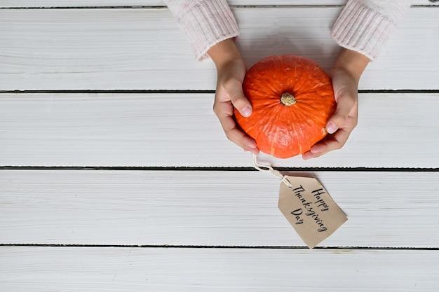 La donna in maglione caldo bianco tiene la zucca arancione matura su fondo bianco