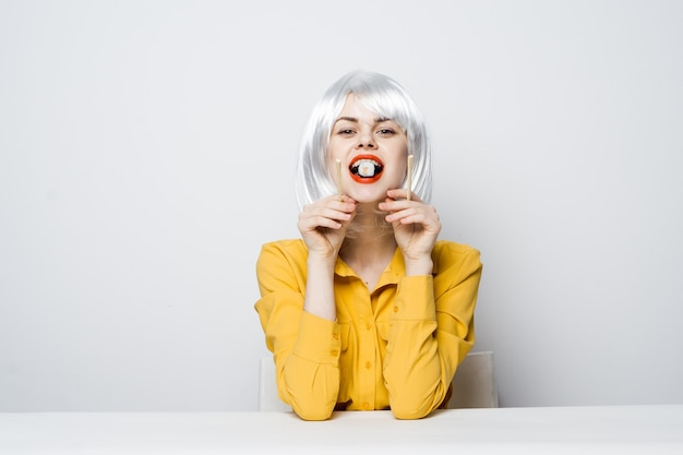 La donna in parrucca bianca rotola le bacchette dell'alimento di dieta dei rotoli di sushi