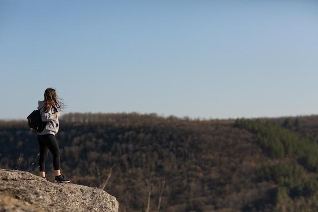 La donna che gli escursionisti gode di una pausa guarda la cima della montagna e della pineta