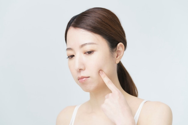 Una donna che si tocca le guance per controllare le condizioni della sua pelle
