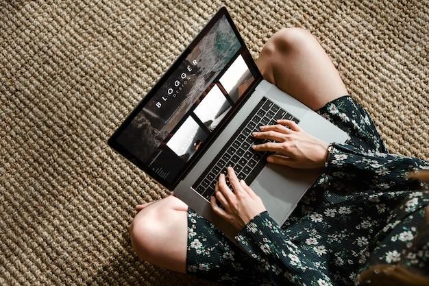 Donna su un tappetino di vimini che usa un laptop