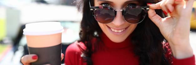 La donna si toglierà gli occhiali da sole e terrà una bevanda calda tra le mani