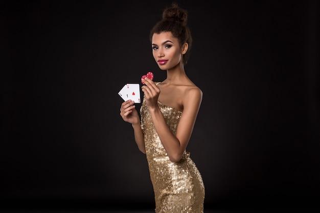 Donna vincente - giovane donna in un elegante abito dorato con due assi e due fiches rosse, una combinazione di carte poker d'assi.