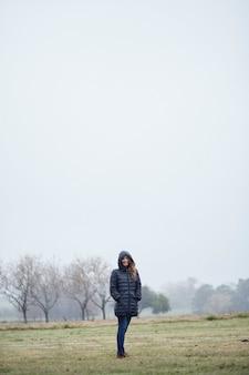 Donna in cappotto invernale in piedi nel campo, tra la nebbia.
