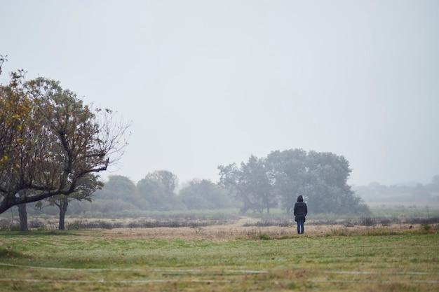 Donna in cappotto invernale in piedi nel campo in lontananza, nella nebbia.