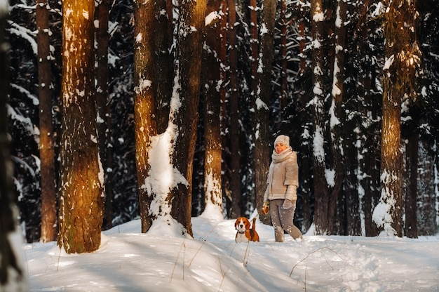 Una donna in una giornata invernale con il suo cane beagle nella foresta invernale giocando.