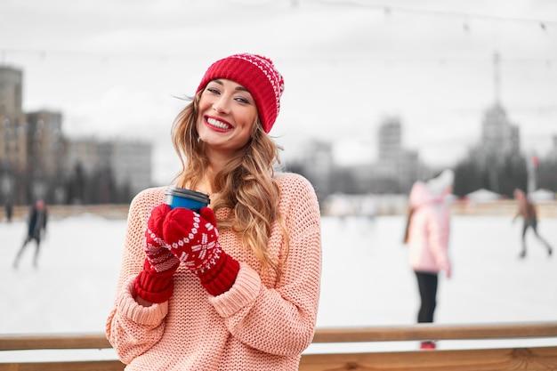 Fondo all'aperto della pista di pattinaggio di ghiaccio di inverno della donna