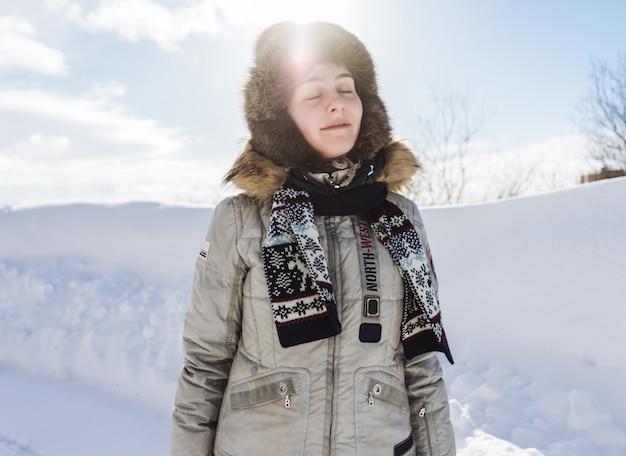 Donna in abito invernale sullo sfondo della neve in una giornata di sole