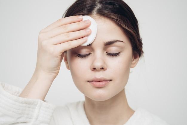 La donna si asciuga il viso con un modello di cura di bellezza in spugna morbida bianca. foto di alta qualità
