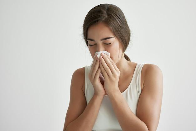 La donna si pulisce il naso con un fazzoletto allergia naso che cola problemi di salute. foto di alta qualità