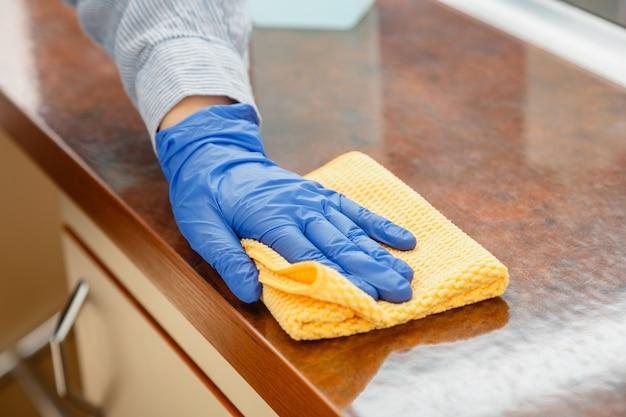 Donna che pulisce il controsoffitto del tavolo in cucina con uno straccio bagnato. la pulizia delle mani della donna delle pulizie femminile disinfetta le superfici del ristorante della casa dell'ufficio.