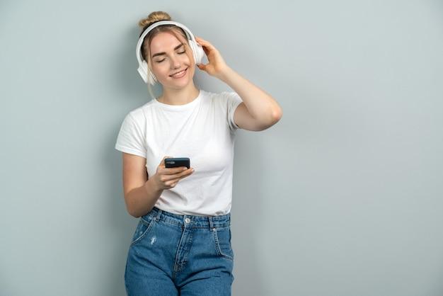 Donna in cuffie senza fili in possesso di un telefono