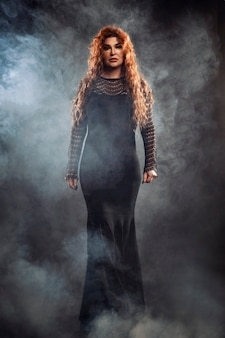 Strega della donna con i capelli rossi in un vestito lungo su un nero