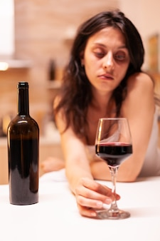 Donna con dipendenza da alcol che tiene la mano sul bicchiere di vino rosso essendo delusa e triste. malattia della persona infelice e ansia che si sente esausta per avere problemi di alcolismo.
