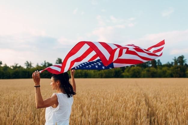 Donna con la bandiera americana nel campo di grano al tramonto il giorno dell'indipendenza di luglio e il concetto di raccolta