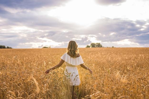Donna con le braccia aperte in un campo di grano.