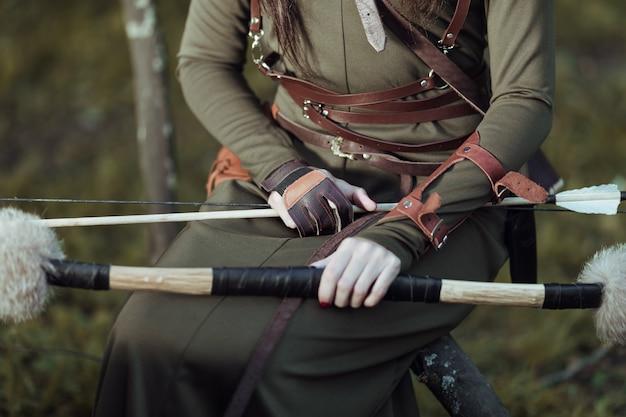 La donna con le frecce e l'arco si siede su un albero caduto, primo piano