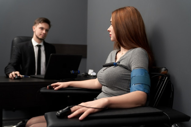 Donna con sensori di collegamento test sul poligrafo del computer.