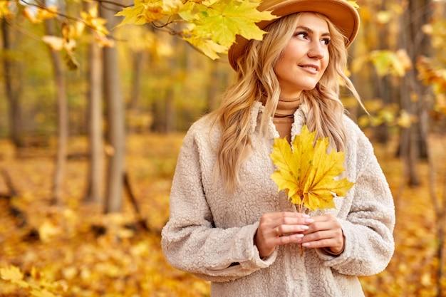 Donna con foglie di autunno nella natura soleggiata, parco o foresta. signora in cappello cammina