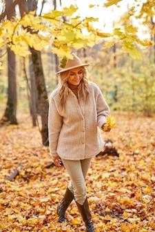 Donna con foglie di autunno nella natura soleggiata, parco o foresta