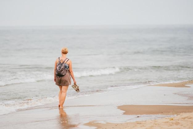 La donna con uno zaino è sulla costa