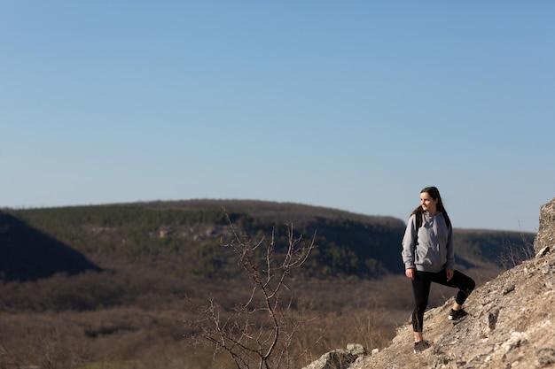 Donna con zaino è in piedi sul bordo della scogliera e sta guardando il paesaggio