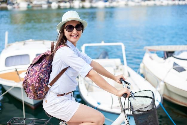 Donna con zaino in sella a bicicletta