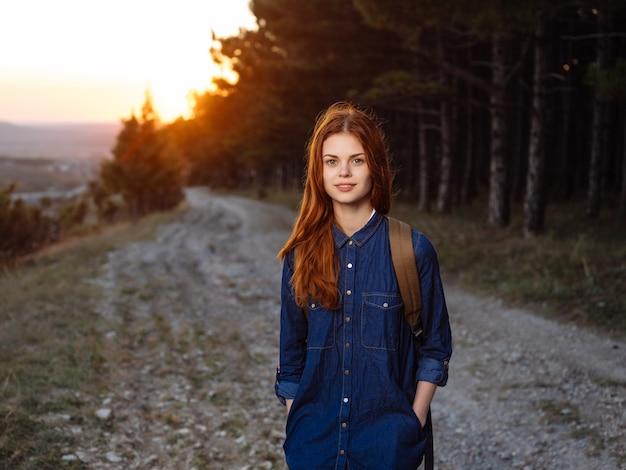 Donna con zaino da viaggio montagne tramonto natura lifestyle