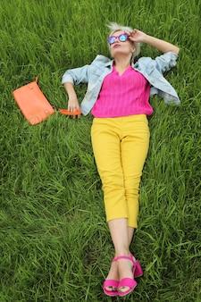 Una donna con una borsa è sull'erba verde in pantaloni gialli e una giacca blu con sandali