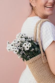 Donna con un sacchetto di fiori di margherite bianche