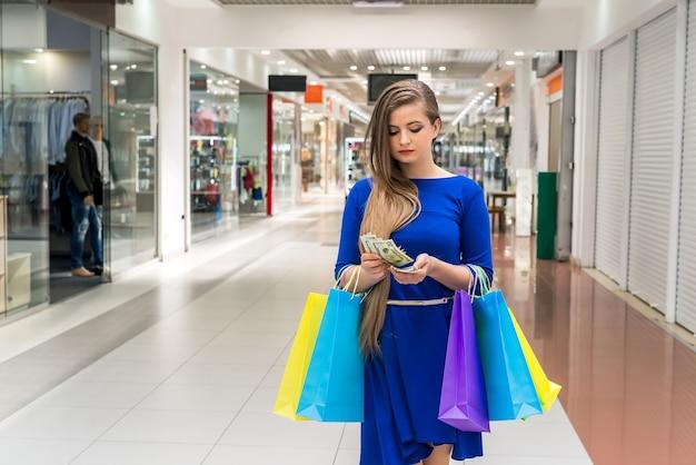 Donna con borse che contano dollari per lo shopping