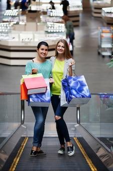 Donna con i sacchetti sulla scala mobile