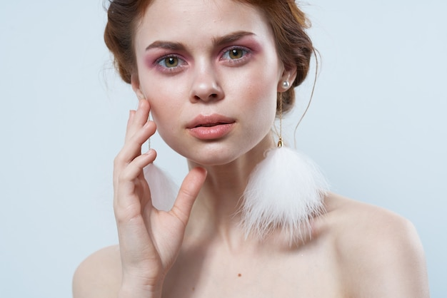 Donna con spalle scoperte e orecchini soffici gioielli trucco luminoso